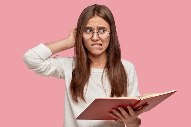 Mujer nerviosa desconcertada se rasca la cabeza, se muerde el labio inferior, no puede memorizar la información necesaria para el seminario, sostiene un libro de texto abierto, se viste con un suéter blanco informal y gafas redondas, modela en interiores