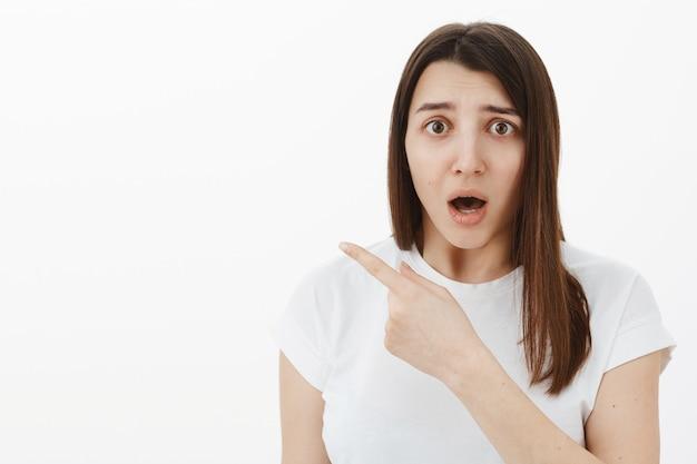 Mujer nerviosa preocupada y conmocionada que parece cuestionada y preocupada con la boca abierta, frunciendo el ceño, angustiada y temblorosa, apuntando a la izquierda a algo injusto o aterrador sobre una pared gris