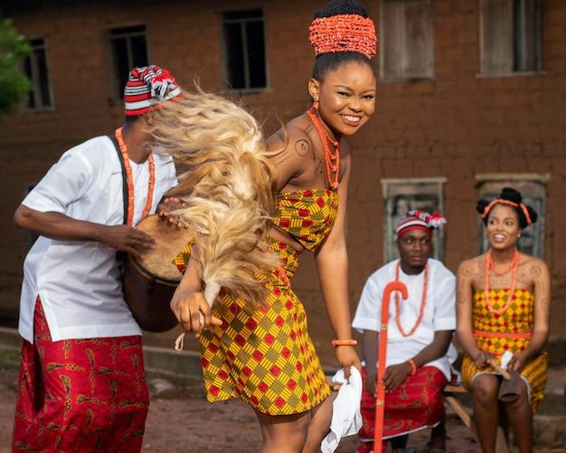 Mujer nigeriana feliz bailando tiro medio
