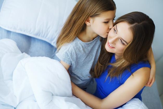Mujer y niña acostada en la cama sonriendo