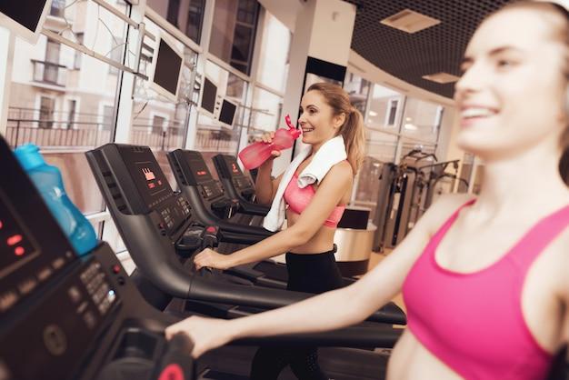 Mujer y niña corriendo en la caminadora en el gimnasio.
