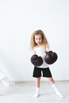 Mujer niña divertida con guantes de boxeo.