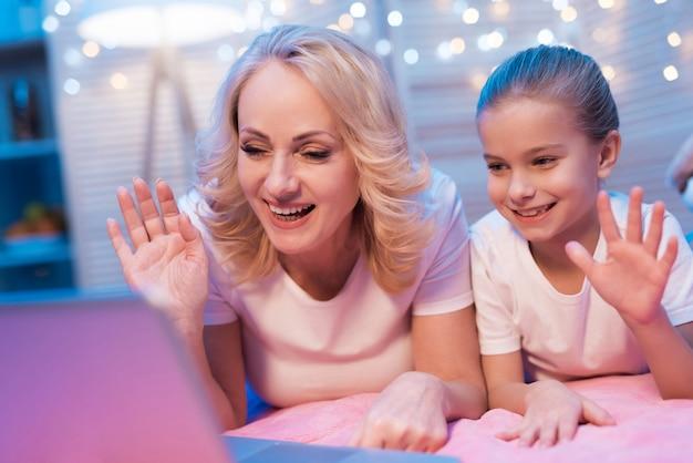 Mujer y niña están hablando con la familia en la computadora portátil