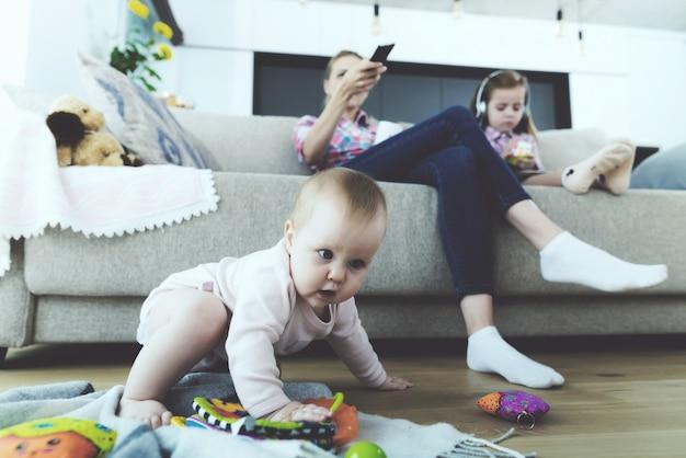 La mujer y la niña están sentadas en el sofá y no siguen al bebé.