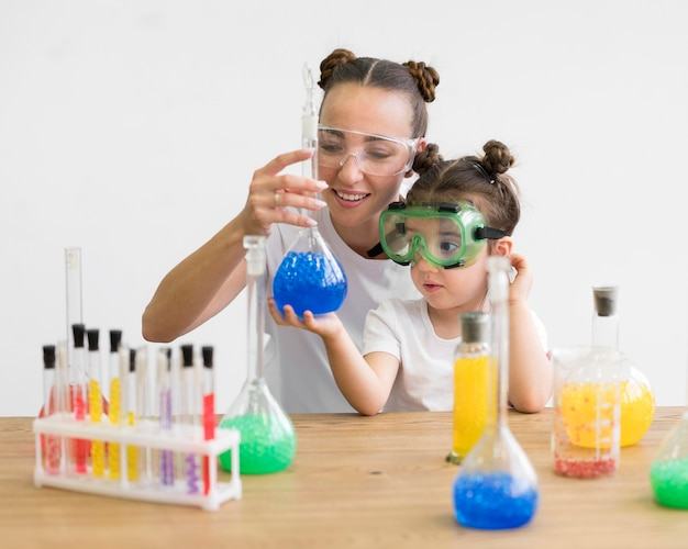 Mujer y niña con gafas de seguridad comprobando experimento
