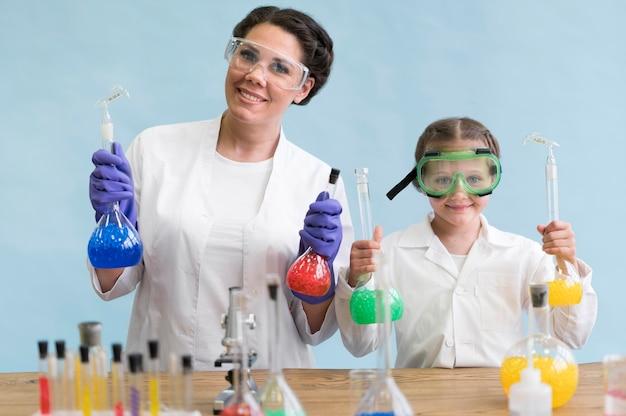 Mujer y niña haciendo ciencia en laboratorio