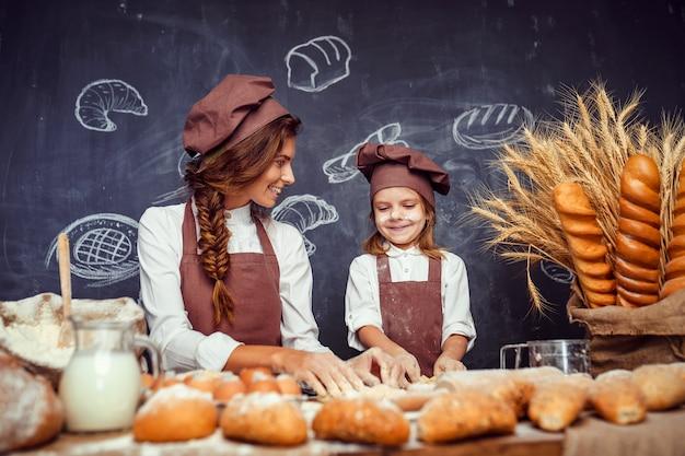 Mujer y niña haciendo pasteles juntos
