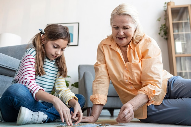 Mujer y niña haciendo rompecabezas en el piso