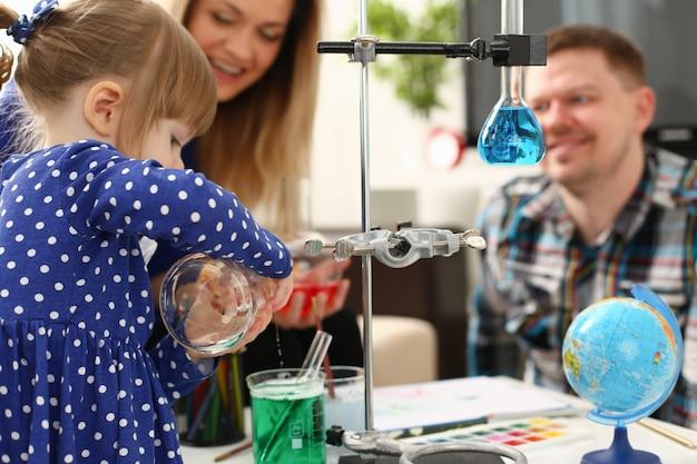 Mujer y niña juegan con líquidos coloridos