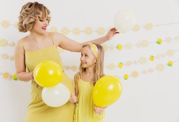 Mujer y niña posando con globos