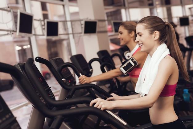 Mujer y niña en ropa deportiva corriendo en cinta en el gimnasio