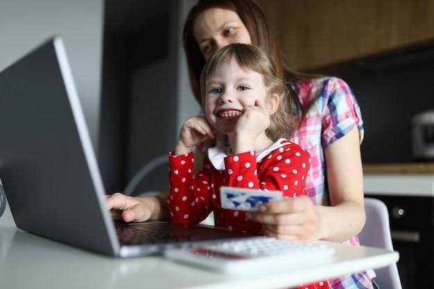 Mujer con niña sentada en la computadora portátil y hacer compras en línea.