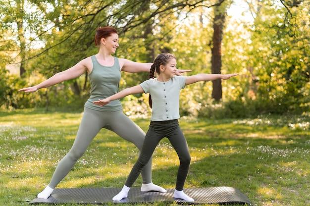 Mujer y niña de tiro completo en estera de yoga