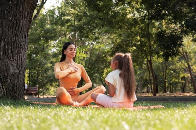 Mujer y niña de tiro completo meditando en el parque