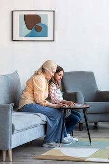 Mujer y niña de tiro completo en la sala de estar