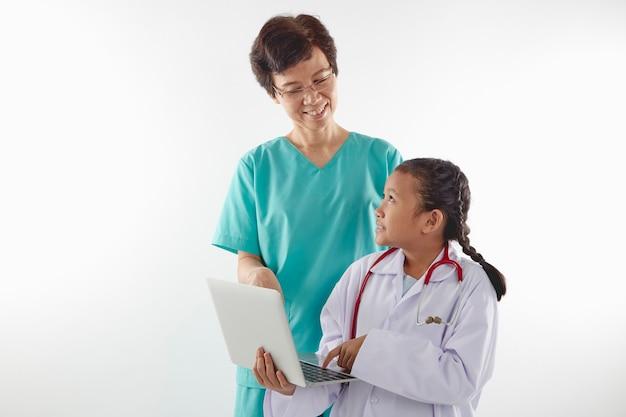 Mujer y niña en trajes de médico charlando