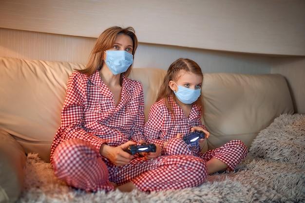 Mujer y niña vistiendo pijamas y máscaras de protección médica sentados en el sofá en la sala de estar con controladores de videojuegos en casa aislamiento cuarentena automática, covid-19