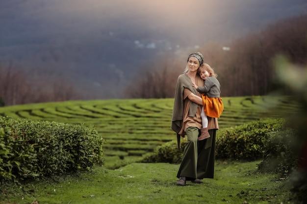 Una mujer con un niño caminando en una plantación de té.
