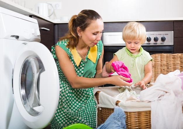 Mujer con niño cerca de la lavadora