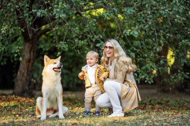 Mujer y niño cerca del perro rojo en el parque otoño