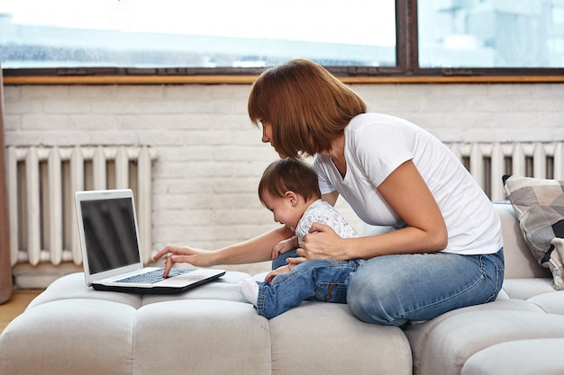 Una mujer con un niño en una computadora portátil sentado en un sofá. trabajo en casa, freelance, trabajo durante la licencia de maternidad para acceso remoto.