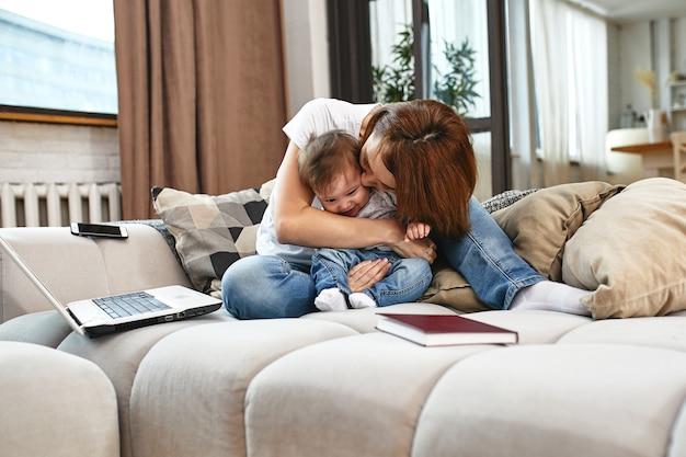 Mujer con un niño en una computadora portátil sentado en un sofá