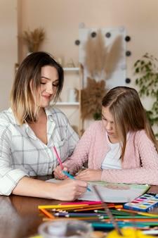 Mujer y niño dibujando juntos plano medio