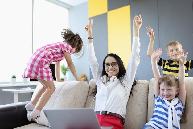 Mujer, niño y dos niñas están sentados en el sofá y riendo alegremente y levantando las manos