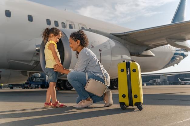 Mujer y niño esperando vuelo cerca del avión blanco