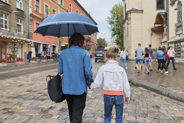 Mujer con niño niña caminando bajo una sombrilla en la calle