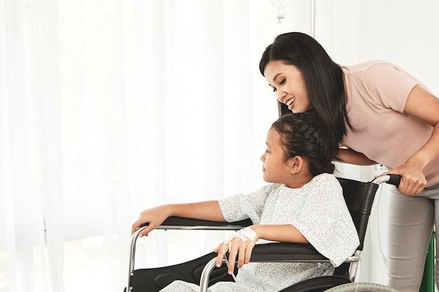 Mujer niño paciente en silla de ruedas