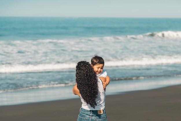 Mujer, con, niño, posición, en, playa