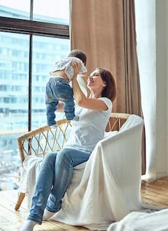 Una mujer con un niño sentado en una silla junto a la ventana. feliz mamá, mamá y bebé. copia espacio