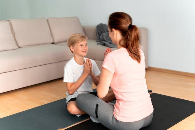 Mujer y niño de tiro completo en estera de yoga