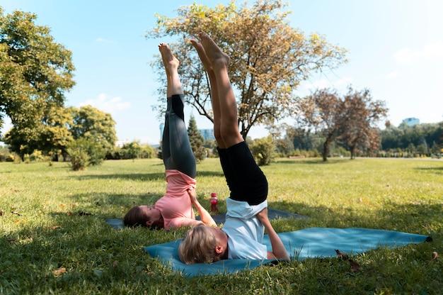 Mujer y niño de tiro completo haciendo yoga