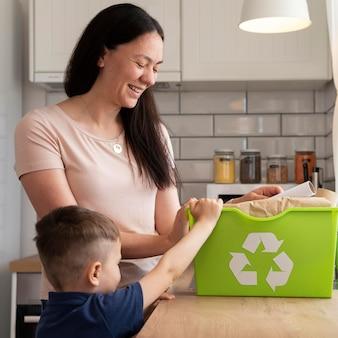 Mujer y niño de tiro medio con papelera de reciclaje