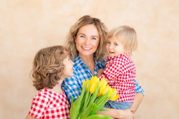 Mujer y niños en casa. madre, hija e hijo se divierten juntos. concepto de vacaciones familiares de primavera. día de la madre