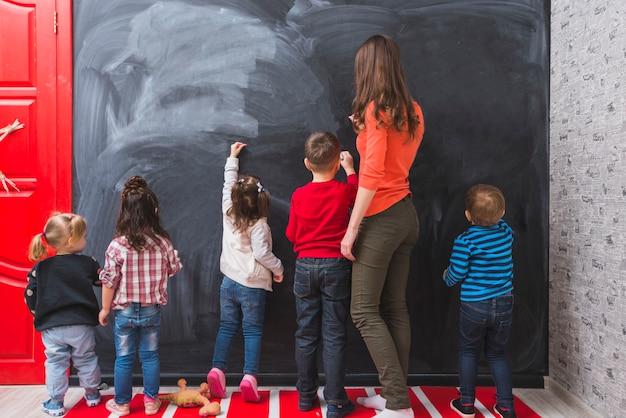Mujer y niños dibujando tiza