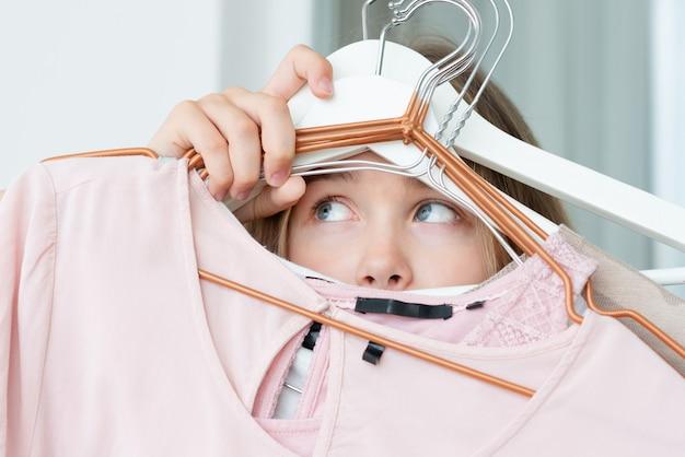 La mujer no puede elegir qué paquete de ropa para viajar. ropa, moda, estilo y concepto de la gente - mujer que elige el guardarropa de la ropa en casa.