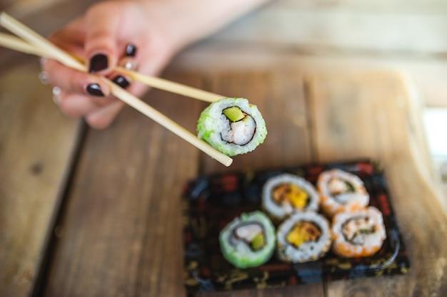 Mujer no reconocida y deliciosos rollos de sushi en la mesa de madera