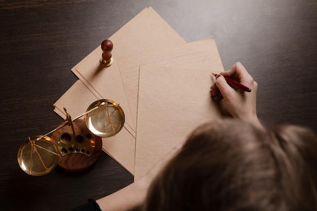 Mujer notaria escribiendo por la pluma en los documentos.