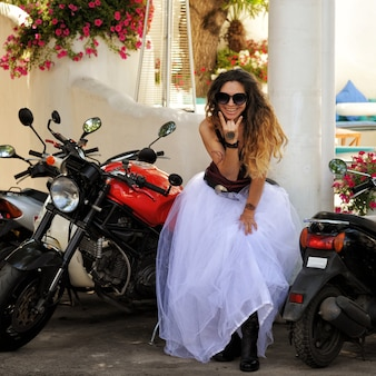 Mujer novia feliz posando con motocicleta, boda de motociclista, al aire libre