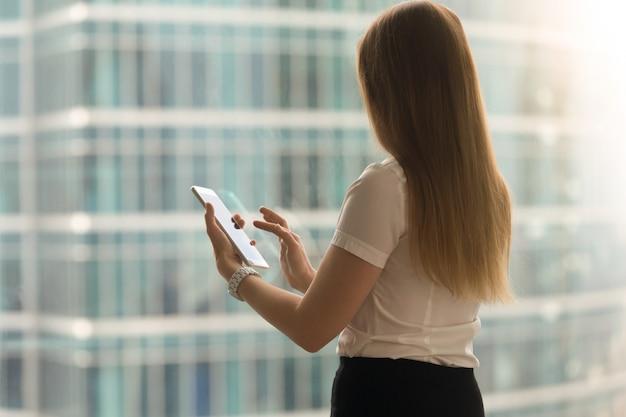 Mujer de nuevo vista deslizar con el dedo en la pantalla de la tableta