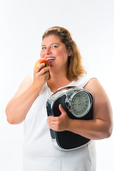 Mujer obesa con escala bajo brazo y manzana.