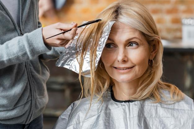 Mujer obteniendo su cabello teñido por peluquero en casa