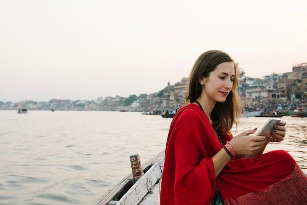 Mujer occidental en un barco enviando mensajes de texto desde el río ganges