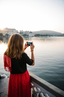 Mujer occidental capturando la vista de la ciudad de udaipur, india