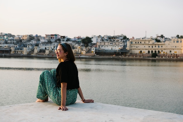 Mujer occidental disfrutando de una vista del lago pushkar en rajasthan
