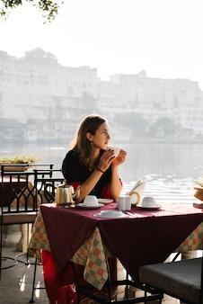 Mujer occidental que tiene un teatime en un café en udaipur