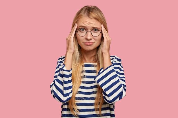 Mujer ocupada con exceso de trabajo estresante con expresión frustrada disgustada mantiene las manos en las sienes